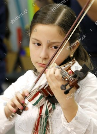 Stock Picture of Belinda Diaz practices her violin during a music class at the Richard Edwards Elementary School, in Chicago. Chicago now joins dozens of school districts across the country in cities like Las Vegas, San Antonio and Tucson, Ariz., that teach mariachi music in schools. It's a way to connect schools and parents, many who speak Spanish, from Hispanic communities says organizers