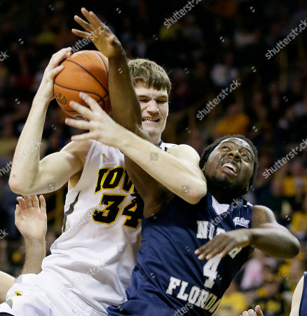 Devin Wilson, Adam Woodbury Iowa center Adam Woodbury, left, battles for a rebound with North Florida guard Devin Wilson during the first half of an NCAA college basketball game, in Iowa City, Iowa