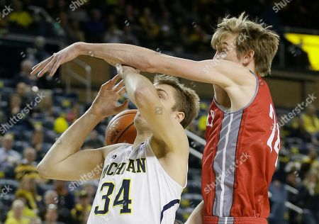 Mark Donnal, Liam Thomas Nicholls State forward Liam Thomas knocks the ball away from Michigan forward Mark Donnal (34) during the first half of an NCAA college basketball game in Ann Arbor, Mich