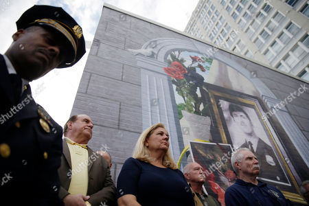 Maureen Faulkner, center, widow of slain Philadelphia police officer Daniel Faulkner, stands with his former cowers and Philadelphia Police First Deputy Commissioner Richard Ross Jr. left, under a new mural of her husband, in Philadelphia. The mural is painted on the side of the police station Faulkner worked at in the Chinatown section of the city. Daniel Faulkner was shot to death by Mumia Abu-Jamal on a downtown street in 1981