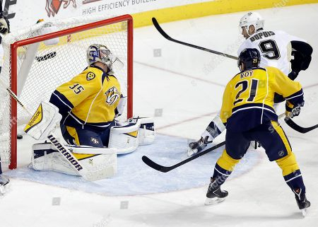 Stock Image of Pekka Rinne, Derek Roy, Pascal Dupuis Pittsburgh Penguins right wing Pascal Dupuis (9) scores against Nashville Predators goalie Pekka Rinne (35), of Finland, in the third period of an NHL hockey game, in Nashville, Tenn. Also defending is Predators' Derek Roy (21
