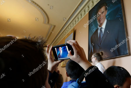 A person takes a photo of the portrait of former Gov. Arnold Schwarzenegger after it was hung on the third floor of the Capitol in Sacramento, Calif., . The portrait of the two-term Republican governor was created by Austrian artist Gottfried Helnwein, who smoothed out a smudge that once featured a lapel button showing the face of wife Maria Shriver