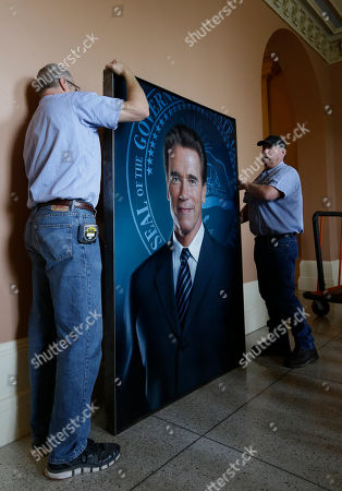 Greg Scarlato, left, and Blake Robison of the Department of General Services, prepare to lift the portrait of former Gov. Arnold Schwarzenegger, into position to be hung on the third floor of the Capitol in Sacramento, Calif., . The official portrait of the two-term Republican governor was created by Austrian artist Gottfried Helnwein, who touched up a smudge on the painting that had one featured the face of Schwarzenegger's wife Maria Schriver