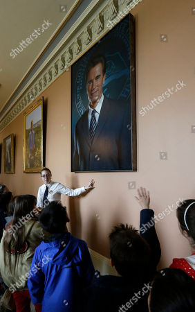Tour guide Alison Parks discusses the portrait of former Gov. Arnold Schwarzenegger with a group of fifth graders after it was hung on the third floor of the the Capitol in Sacramento, Calif., . The portrait of the two-term Republican governor was created by Austrian artist Gottfried Helnwein, who smoothed out a smudge that once featured a lapel button showing the face of wife Maria Shriver