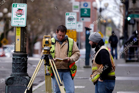 Surveyors Chris Fox, left, and Zach Cloe record measurements at a benchmark for settling of nearby buildings, in Seattle's Pioneer Square neighborhood. The Seattle City Council expects to learn more Monday about the extent of problems from the attempt to repair the machine that broke down while boring a highway tunnel under the city. State Transportation Department officials will brief the council about cracks in streets and buildings and settling by buildings in the Pioneer Square area near the Alaskan Way Viaduct