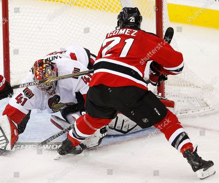 Craig Anderson, Scott Gomez Ottawa Senators goalie Craig Anderson (41) blocks a shot by New Jersey Devils center Scott Gomez (21) during the third period of an NHL hockey game, in Newark, N.J. The Senators won 2-0