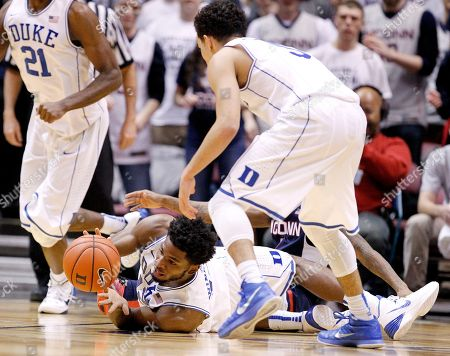 Justise Winslow, Tyus Jones Duke forward Justise Winslow, bottom, passes the ball to Tyus Jones, front right, while competing for the ball against Connecticut guard Ryan Boatright (not shown) during the second half of an NCAA college basketball game, in East Rutherford, N.J. Duke won 66-56