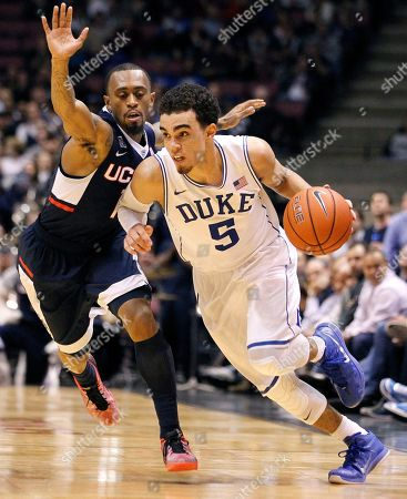 Stock Picture of Tyus Jones, Ryan Boatright Duke guard Tyus Jones (5) drives against Connecticut guard Ryan Boatright during the second half of an NCAA college basketball game, in East Rutherford, N.J. Duke won 66-56