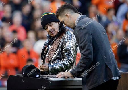 Musician Carlos Santana and his son, Salvador Santana perform the national anthem before Game 4 of baseball's World Series between the Kansas City Royals and the San Francisco Giants, in San Francisco