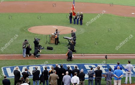 Stock Image of Musician Carlos Santana and his son, Salvador Santana perform the national anthem before Game 4 of baseball's World Series between the Kansas City Royals and the San Francisco Giants, in San Francisco