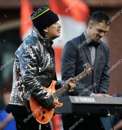 Musician Carlos Santana and his son, Salvador Santana, perform the national anthem before Game 4 of baseball's World Series, in San Francisco