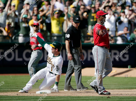 Nick Punto, Luis Jimenez Oakland Athletics' Nick Punto, left, slides safely into third base with an RBI triple next to Los Angeles Angels third baseman Luis Jimenez during the seventh inning of a baseball game, in Oakland, Calif