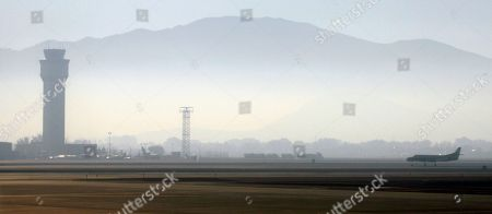 "Stock Image of Smoke hangs over Reno-Tahoe International Airport as a plane takes off on in Reno, Nev. Crews in California have been fighting the King Fire, east of Sacramento, which is threatening thousands of homes and prompting ""dense smoke advisories"" across the region"