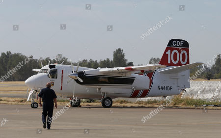 """Bill Payne, senior air operations officer for the California Department of Forestry and Fire Protection, walks out to an S-2T air tanker on the tarmac at the CalFire Aviation Management facility, in Sacramento, Calif., . CalFire Director Ken Pimlott announced Friday, that CalFire's fleet of 22 S-2 tankers were cleared to return to duty after they were grounded earlier this week following the death of pilot Geoffrey """"Craig"""" Hunt when his plane smashed into a canyon wall while dropping retardant on a fire near Yosemite National Park's west entrance. CalFire lifted the safety stand-down for the state airplanes after federal investigators found the tanker crash did not involve structural failure or aging aircraft issues"""