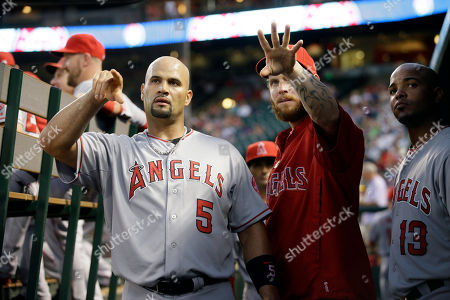 """Josh Hamilton, Albert Pujols, Luis Jimenez Los Angeles Angels' Albert Pujols (5), Josh Hamilton, center, and Luis Jimenez, right, talk in the dugout as they look to left field during a baseball game against the Texas Rangers in Arlington, Texas. Philadelphia Phillies pitcher Jerome Williams was with the Los Angeles Angels a few seasons ago when star slugger Albert Pujols took the initiative to institute an informal clubhouse rule keeping players off their phones for the first 20 to 30 minutes after the end of a game. """"Albert wanted us to take the time immediately after a game to think about what happened out there,"""" Williams said"""