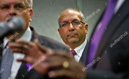 Oscar Michelen, center, the attorney for convicted murderer David McCallum, listens as Brooklyn District Attorney Ken Thompson speaks during a press conference on in New York. Thompson said he will ask a judge to throw out the convictions of McCallum and the late Willie Stuckey, saying their murder convictions hinged on made-up confessions peppered with details seemingly supplied by police