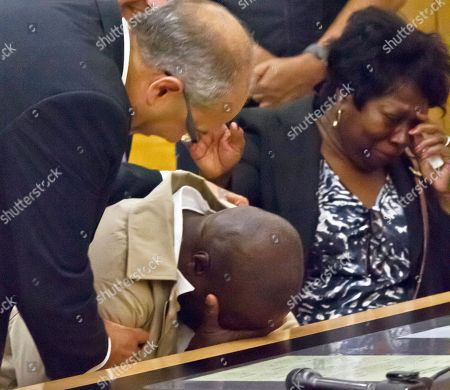 Defense attorney Oscar Michelen, left, comforts his client David McCallum, center, as he weeps along with Rosia Nealy, right, the mother of Willie Stuckey, in Brooklyn's Supreme Court, in New York. McCallum and Stuckey, who died in prison, were 16 years old when they were convicted of murder. A judge exonerated both men for wrongful conviction