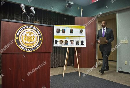 A time-line photo board of individuals exonerated in wrongful conviction cases is displayed, as Brooklyn District Attorney Ken Thompson arrive for a news conference, in New York. Thompson will ask a judge to throw out the convictions of David McCallum and the late Willie Stuckey, saying their convictions hinged on made-up confessions peppered with details seemingly supplied by police