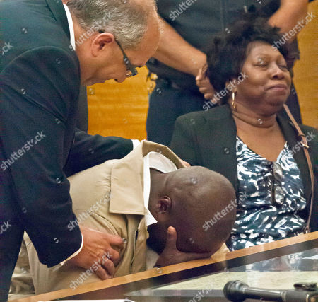 Defense attorney Oscar Michelen, left, comforts his client David McCallum, center, as he weeps, while Rosia Nealy, right, the mother of Willie Stuckey, smile after a judge's decision in Brooklyn's Supreme Court, in New York. McCallum and Stuckey, who died in prison, were 16 years old when they were convicted of murder. A judge exonerated both men for wrongful conviction