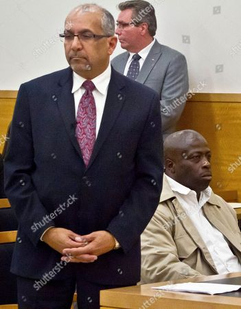 Defense attorney Oscar Michelen, left, and his client David McCallum, right, listen to remarks in Brooklyn's Supreme Court, in New York. McCallum and Willie Stuckey, who died in prison, were 16 years old when they were convicted of murder. A judge exonerated both men for wrongful conviction