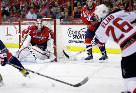 Stock Photo of Braden Holtby, Patrik Elias Washington Capitals goalie Braden Holtby (70) prepares to block a shot by New Jersey Devils left wing Patrik Elias (26), from the Czech Republic, in the second period of an NHL hockey game, in Washington