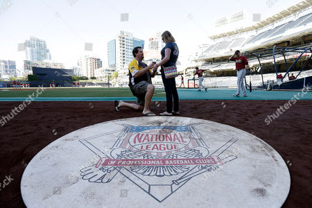 Stock Photo of Jeremy Patterson, Courtney Walsh Jeremy Patterson, left, proposes to Courtney Walsh during batting practice before the San Diego Padres play the Arizona Diamondbacks in a baseball game, in San Diego