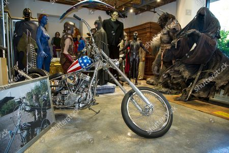 "A vintage ""Easy Rider Captain America"" motorcycle is shown surrounded by Hollywood memorabilia in Calabasas, Calif. The auction house Profiles in History estimates the Harley-Davidson will bring a minimum of $1 million at its Oct. 18, 2014 sale. Its principal authentication comes from ""Grizzly Adams"" actor Dan Haggerty, who had a bit part in ""Easy Rider"" and claims to have taken possession of the only bike that survived the filming of the druggy road movie. But Haggerty admitted this week, in an interview with Los Angeles Times, that he has authenticated and sold two Captain America bikes"