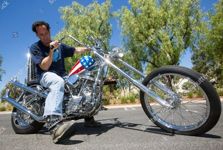 """Michael Eisenberg Michael Eisenberg, sits on the customized Captain America chopper Peter Fonda rode in """"Easy Rider"""" at the Profiles in History auction house in Calabasas, Calif. Eisenberg, a California businessman who once co-owned a Los Angeles motorcycle-themed restaurant with Fonda and """"Easy Rider"""" co-star Dennis Hopper, owns the motorcycle that has come to symbolize the counterculture of the 1960s. The auction house Profiles in History tells The Associated Press it estimates the Harley-Davidson will bring between $1 million and $1.2 million at its Oct. 18, 2014 sale. AP Photo/Damian Dovarganes"""