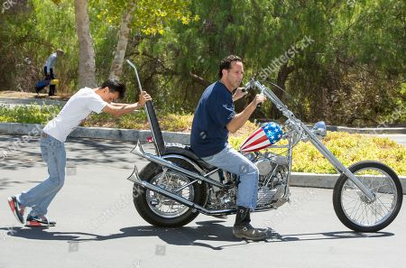 """Stock Image of Michael Eisenberg Michael Eisenberg, right, is helped to move the customized Captain America chopper Peter Fonda rode in """"Easy Rider"""" at the Profiles in History auction house in Calabasas, Calif. Eisenberg, a California businessman who once co-owned a Los Angeles motorcycle-themed restaurant with Fonda and """"Easy Rider"""" co-star Dennis Hopper, owns the motorcycle that has come to symbolize the counterculture of the 1960s. The auction house Profiles in History tells The Associated Press it estimates the Harley-Davidson will bring between $1 million and $1.2 million at its Oct. 18, 2014 sale. AP Photo/Damian Dovarganes"""