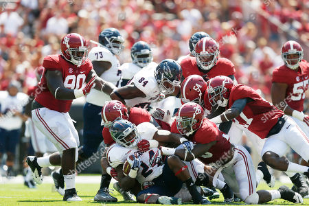 Stock Image of Alabama's defense takes down Florida Atlantic running back Tony Moore (24) in the first half of an NCAA college football game, in Tuscaloosa, Ala