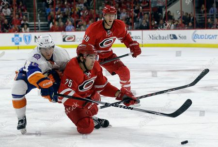 Riley Nash, Chris Terry, Thomas Hickey New York Islanders' Thomas Hickey (14) and Carolina Hurricanes' Chris Terry (25) chase the puck as Hurricanes' Riley Nash (20) watches at rear during the second period of an NHL hockey game in Raleigh, N.C