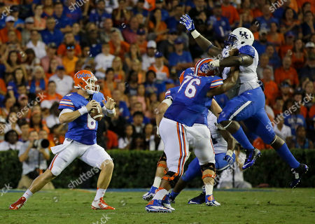 Florida quarterback Jeff Driskel (6) looks for a receiver as he gets a block from offensive linesman Max Garcia (76) against Kentucky defensive tackle Melvin Lewis, right, during the first half of an NCAA college football game in Gainesville, Fla