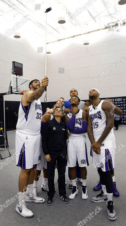 """Sim Bhular, Ray McLemore, Vivek Ranadive, Nick Stauskas, Ryan Hollins, Ben McLemore, DeMarcus Cousins Sacramento Kings rookie center, Sim Bhular, of Canada, left, holds the camera as members of the team take a """"selfie"""" during the Kings media day in Sacramento, Calif., . In the front row are Kings majority owner Vivek Ranadive, second from left, Ben McLemore third from left, and DeMarcus Cousins, right, In the background are Ray McCallum, behind Ranadive, Nick Stauskas, and Ryan Hollins, behind McLemore"""