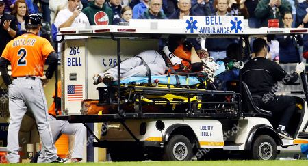 Stock Image of Giancarlo Stanton On, Miami Marlins third base coach Brett Butler watches as Giancarlo Stanton is taken off the field after being hit by a pitch during the fifth inning of a baseball game against the Milwaukee Brewers in Milwaukee. Stanton sustained multiple facial fractures, dental damage and cuts that needed stitches after being hit in the face by a fastball from Milwaukee's starting pitcher Mike Fiers