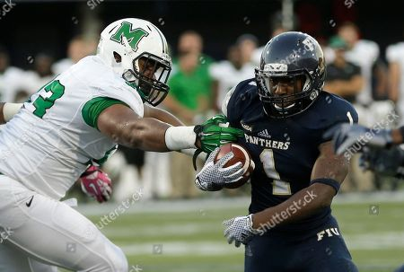 Stock Photo of Alex Gardner, Steve Dillon Florida International running back Alex Gardner (1) drives as Marshall defensive lineman Steve Dillon (93) defends during the first half of an NCAA college football game, in Miami