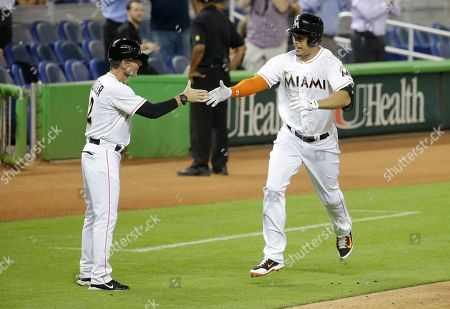 Giancarlo Stanton, Brett Butler Miami Marlins' Giancarlo Stanton, right, is congratulated by third base coach Brett Butler, left, after hitting a two-run home in the third inning during a baseball game against the New York Mets, in Miami