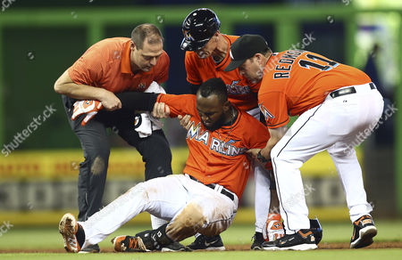 Stock Picture of Marcell Ozuna Miami Marlins manager Mike Redmond (11) and third base coach Brett Butler, top center, along with a trainer help Marcell Ozuna to his feet after he hurt his leg during the seventh inning of a baseball game against the Washington Nationals in Miami, . The Nationals won 2-1