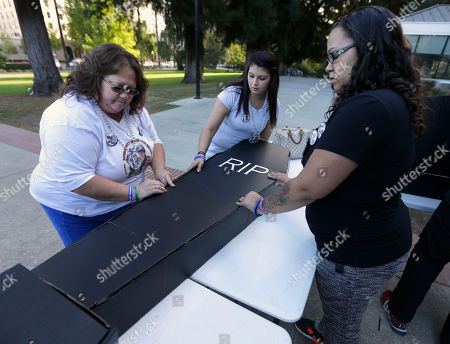Tammie Burns, left, the mother of Charles Burns, who was shot and who was shot and killed by Concord, Calif, Police officers in 2013, gets help assembling a replica casket from Gloria Cisneros, center and Ciara Brown during a demonstration against police brutality, at the Capitol in Sacramento, Calif. Dozens of protectors rallied against what they say is excessive use of force by police. Burns' family has filed a federal civil rights lawsuit, alleging the use of excessive force, against the city of Concord, Concord Police Chief Guy Swanger, as well as Contra Costa County and the district attorney's office