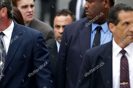 """Giuseppe """"Joe"""" Giudice, Teresa Giudice The Real Housewives of New Jersey"""" star Giuseppe """"Joe"""" Giudice, 43, center, and his wife, Teresa Giudice, 41, not seen, walk behind men while leaving the Martin Luther King, Jr. Courthouse after a court appearance, in Newark, N.J. Teresa Giudice was sentenced Thursday in federal court to 15 months in prison on conspiracy and bankruptcy charges while her husband, Giuseppe """"Joe"""" Giudice, was sentenced to 41 months. Together they must pay $414,000 in restitution"""