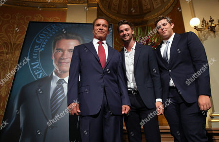 Arnold Schwarzenegger, Patrick Schwarzenegger, Christopher, 16 Former Gov. Arnold Schwarzenegger poses with his sons Patrick, 20, center and Christopher, 16, in front of his official portrait after it was unveiled at the Capitol in Sacramento, Calif., . The photograph-like giant image of the former governor was done by Austrian artist Gottfried Helnwein and will hang on the third floor of the Capitol