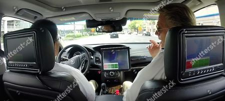 Peter Carey, right, talks during a driving demonstration in a prototype Acura RLX sedan in Detroit, . The car has cameras that monitor lane marking and multiple radar sensors on the front and sides. On top is a beacon that uses laser beams to continually scan the car's surroundings, similar to self-driving prototypes already introduced by Google, Ford and Toyota. GPS also helps the car stay on a previously mapped course and follow the speed limit
