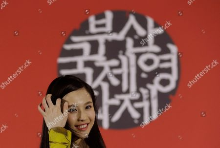 """Zhang Huiwen Chinese actress Zhang Huiwen smiles during a press conference to promote her movie """"Coming Home"""" at the Busan International Film Festival in Busan, South Korea, . The letters in the background read """"Busan Film Festival"""