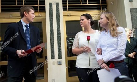 Stock Photo of Paul Ferguson, Jennifer Melsop, Erika Turner Clerk of the Circuit Court of Virginia Paul Ferguson, left, makes an announcement outside the Arlington County Courthouse in Arlington, Va., granting the very first marriage license application to Jennifer Melsop, 26, center, and Erika Turner, 26, in front of the Arlington County Courthouse in Arlington, Va., Monday, Oct. 6, 2014. The Supreme Court cleared the way Monday for an immediate expansion of same-sex marriage by unexpectedly and tersely turning away appeals from five states seeking to prohibit gay and lesbian unions. The court's order effectively makes gay marriage legal in 30 states