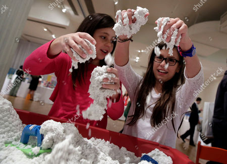 Stock Picture of Rylie Klein, left, and Madison Shipman play with Sands Alive!, from Play Visions, at the TTPM Holiday Showcase, in New York