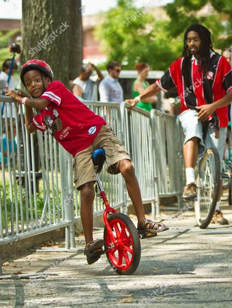 "Iredike Erima, 9, left, hangs onto a training rail as he struggles to balance on a unicycle, as his father Sharai Erima, right, trails behind during the 2014 NYC Unicycle Festival, on Governors Island in New York. ""Our family decided to try something new,"" said Sharai. In its fifth year, the event brings together first time riders, as well as recreational riders and world-class performers. ""It's one of the few things parents and kids try,"" said festival director Keith Nelson. ""When you see families doing things together it's beautiful"