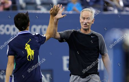 John McEnroe John McEnroe high-fives a ball boy as during an exhibition match prior to the quarterfinal between Roger Federer and Gael Monfils at the U.S. Open tennis tournament, in New York. McEnroe and James Blake played Mats Wilander and Jim Courier