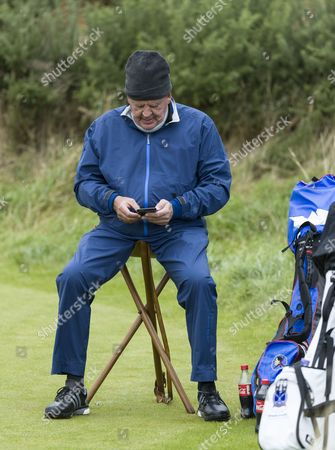 Stock Image of Johann Rupert sits on a three-legged stool on the 10th tee at Kingsbarns Golf Links during day 2 of The Alfred Dunhill Links Championship, Scotland on 7th October
