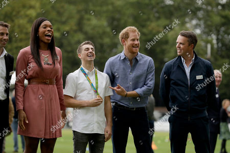 Stock Image of Britain's Prince Harry, second right, jokes with photographers as he poses in a group photograph with, from left, England netball player Eboni Beckford-Chambers, double-Olympic gold medalist gymnast Max Whitlock and former England cricket player Graeme Swann during an event to mark the expansion of the Coach Core sports coaching apprenticeship programme at Lord's cricket ground in London, . Coach Core helps to inspire young people to build a career in sports coaching
