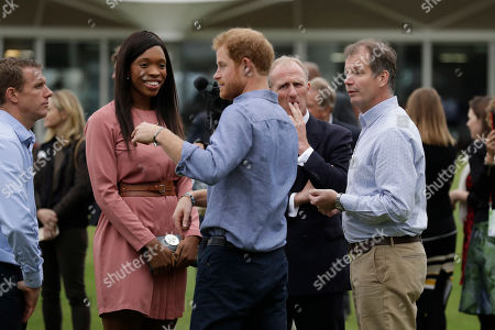 Stock Photo of Britain's Prince Harry, centre, chats with England netball player Eboni Beckford-Chambers, second left, during an event to mark the expansion of the Coach Core sports coaching apprenticeship programme at Lord's cricket ground in London, . Coach Core helps to inspire young people to build a career in sports coaching