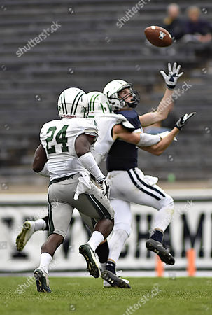 Yale Wide Receiver number 14, Reed Klubnik readies to make a catch while being pursued by Dartmouth's number 5, Charlie Miller and number 24, Jarius Brown during the NCAA football game between the Dartmouth Big Green and Yale Bulldogs at the Yale Bowl in New Haven Connecticut. Yale won the game 21 to 13